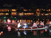 Les touristes prennent du plaisir à lâcher des lanternes sur la rivière Hoài