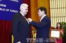 Insigne «Pour la cause des sciences sociales du Vietnam» au Premier ministre turc