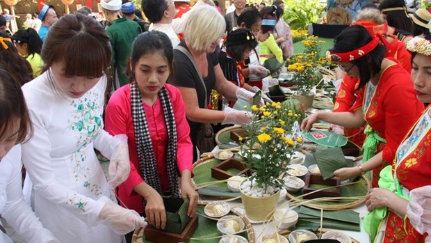 Des touristes etrangers font l'experience du Tet vietnamien avec le festival du