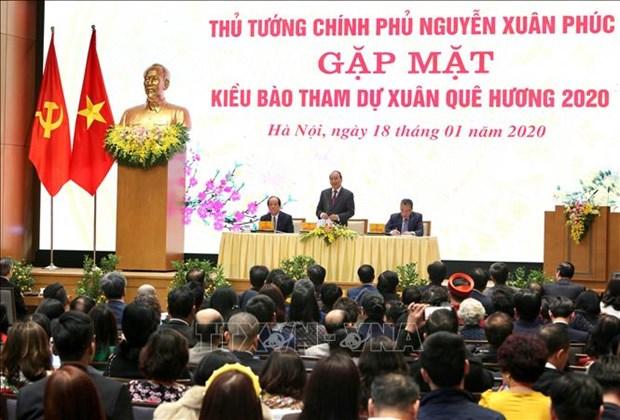Rencontre entre le Premier ministre et des Viet kieu de retour au pays pour le Tet hinh anh 1
